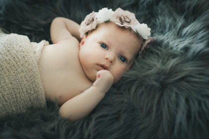 Babyshooting Neugeborenes Maedchen Blumen Fell